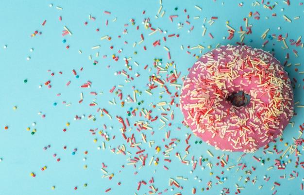 Beignet (beignet) de différentes couleurs sur fond bleu avec des pépites de sucre festives multicolores. vacances et bonbons, cuisson pour les enfants, concept de sucre