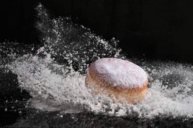 Beignet berlinois avec de la confiture farcie tombe dans la farine