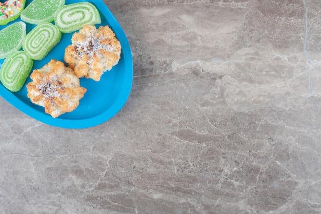 Un beignet, des biscuits et des confitures sur un petit plateau sur une surface en marbre