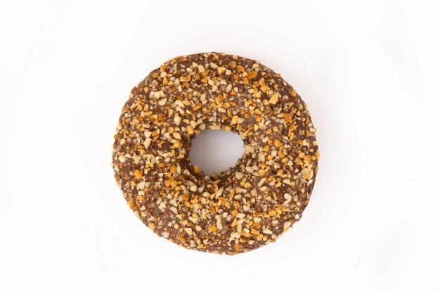 Beignet brun aux noix sur une surface blanche.