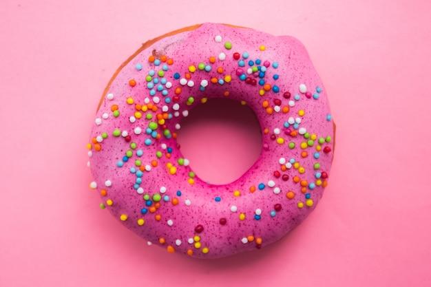 Beignet de cercle fait maison avec glaçage rose et pépites d'arc-en-ciel