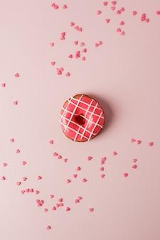 Un beignet de colar et un coeur rose en forme de coeur sur fond rose, monochrome