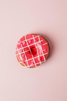 Un beignet de colar vivant avec des pépites en forme de cœur sur fond rose, monochrome