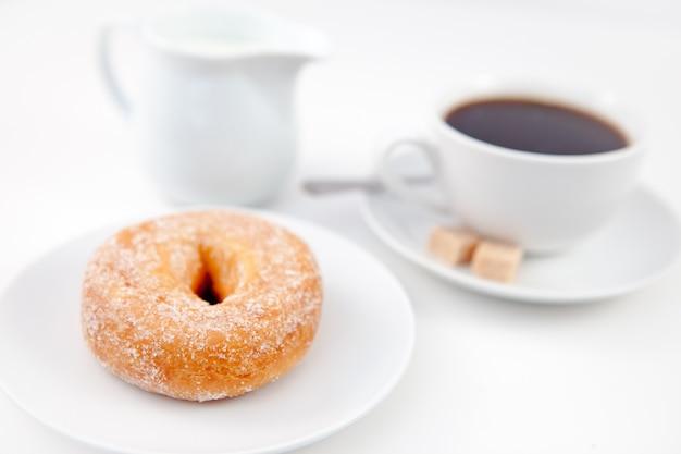 Beignet avec du sucre glace et une tasse de café sur des assiettes blanches avec du sucre et du lait