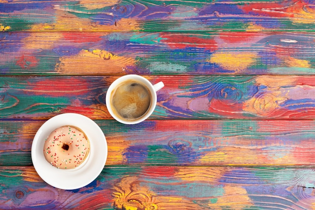 Beignet frais avec du café sur une surface en bois, vue de dessus