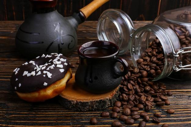 Beignet avec glaçage noir et chocolat en poudre et une authentique tasse de café fort. une boîte de grains de café et de céréales coulées.