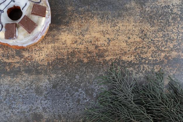 Beignet glacé et une branche de pin sur une surface en marbre