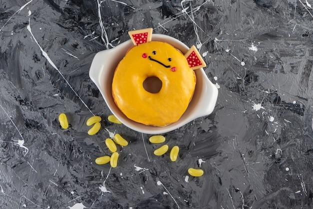 Beignet glacé jaune avec des bonbons de haricots placés sur une table en marbre.