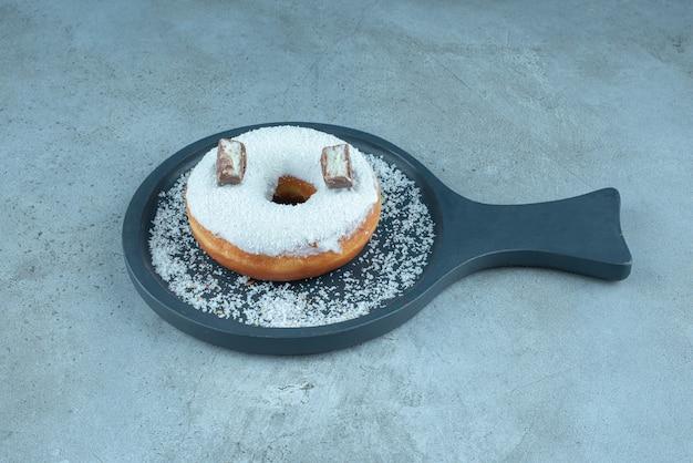 Beignet glacé placé dans un plat de service sur du marbre.