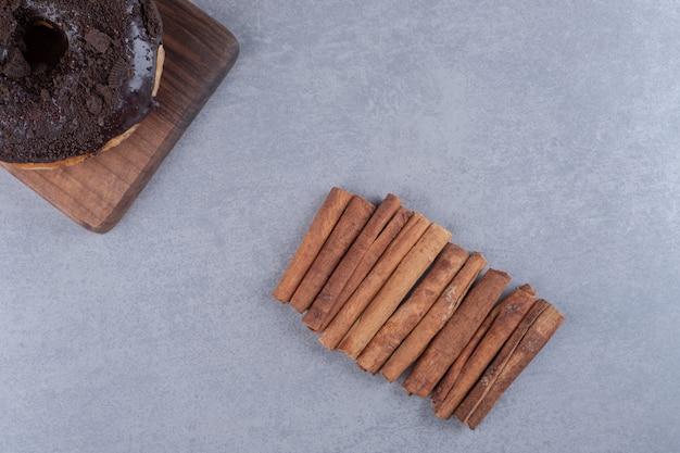 Un beignet et un paquet de bâtons de cannelle sur une surface en marbre