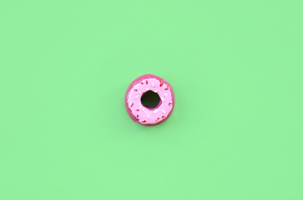 Beignet en plastique simple petit se trouve sur un fond coloré pastel