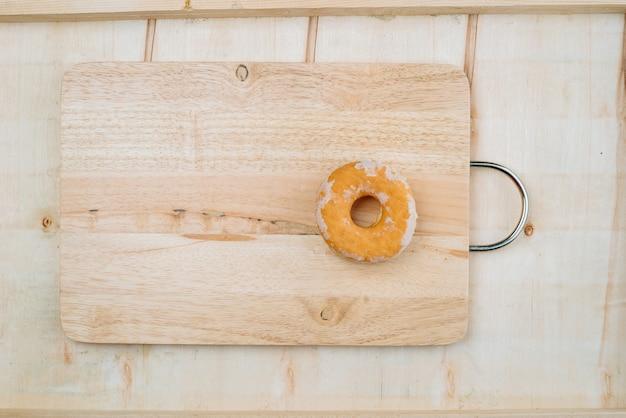 Un beignet rond sur une planche de bois