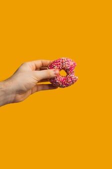 Beignet rose dans une main sur fond jaune