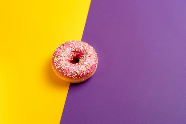 Beignet rose sur le mur violet foncé jaune et violet vue de dessus copie espace