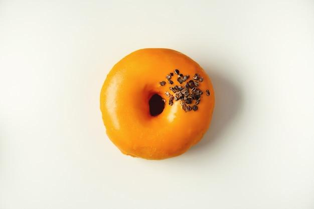 Beignet sucré glacé à l'orange et chocolat sur fond gris. donut savoureux sur la texture béton pastel
