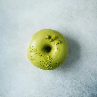 Beignet sucré avec glaçure verte et pistache sur gris. donut savoureux sur la texture de béton pastel, espace copie, vue de dessus