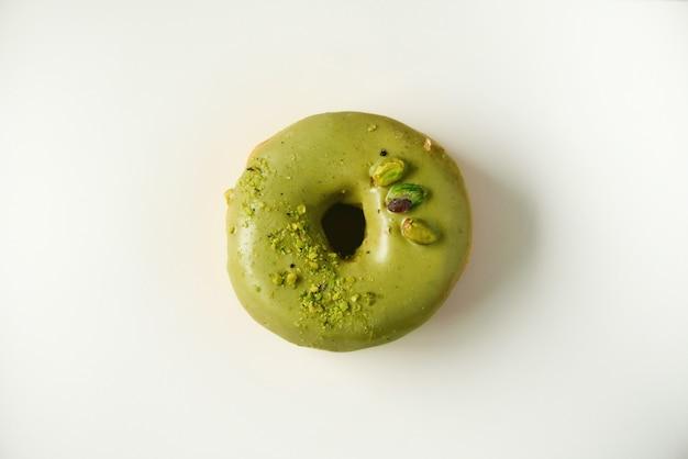 Beignet sucré avec glaçure verte et pistache sur gris. donut savoureux sur la texture béton pastel