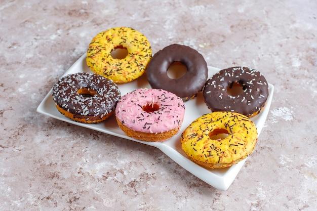 Beignets assortis avec glaçage au chocolat, glaçage rose et vermicelles.