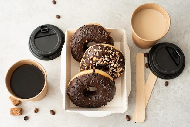 Beignets au chocolat avec glaçage dans une boîte artisanale et café noir dans des tasses sur un tableau blanc