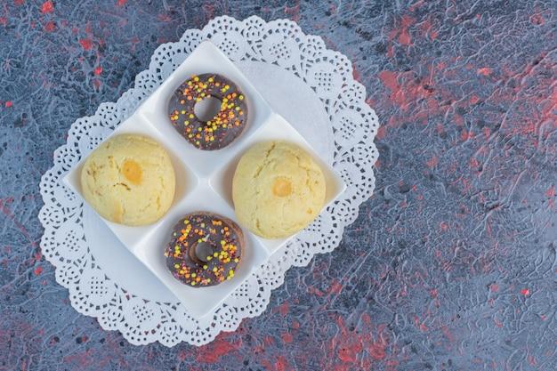 Des beignets et des biscuits de la taille d'une collation sur un plateau de service sur un napperon sur une table abstraite.