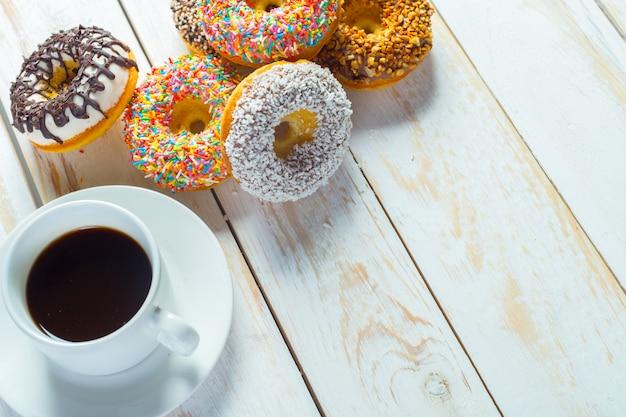 Beignets et café sur un fond de bois blanc.