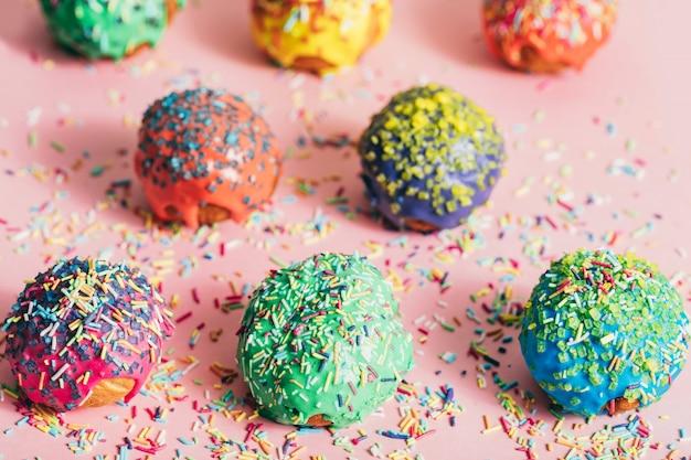 Beignets colorés avec des brins de sucre sur un fond en désordre