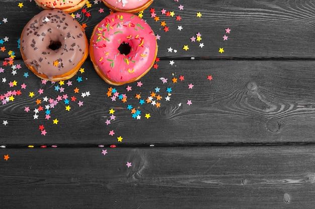 Beignets colorés décorés avec des confettis saupoudrent sur un fond en bois foncé