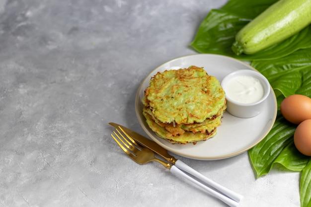 Beignets de courgettes, beignets végétariens de courgettes, servis avec des herbes fraîches et de la crème sure.