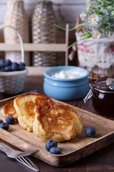 Beignets avec crème sure, confiture et bleuets. le plat russe traditionnel. fermer.