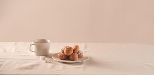 Beignets avec du sucre sur une assiette et une tasse de café sur fond blanc