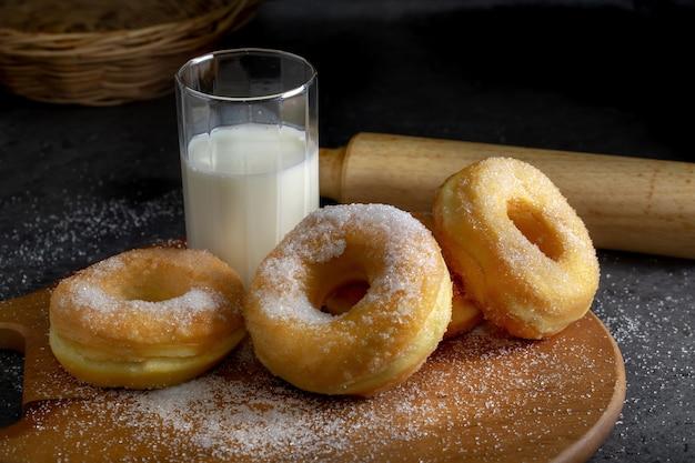 Beignets avec du sucre sur une plaque de bois sur un fond de table sombre.