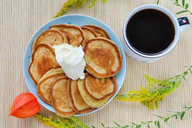 Beignets de farine de seigle avec crème sure et café.