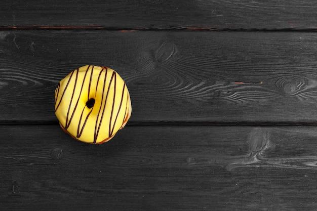 Beignets frais colorés sur une surface en bois noire foncée