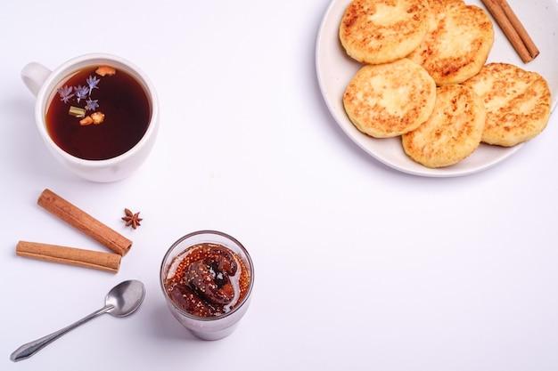 Beignets de fromage cottage avec confiture de figues et thé aromatique noir chaud, ambiance de petit-déjeuner d'hiver avec anis et cannelle