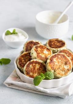 Beignets de fromage cottage avec pois verts, aneth, menthe et sauce. petit-déjeuner sain ou déjeuner diététique.