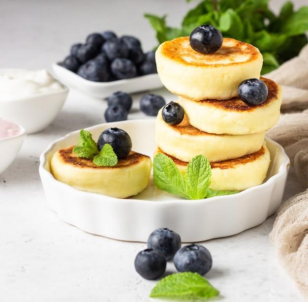 Beignets de fromage cottage (syrniki) avec myrtilles fraîches, menthe et sauce.