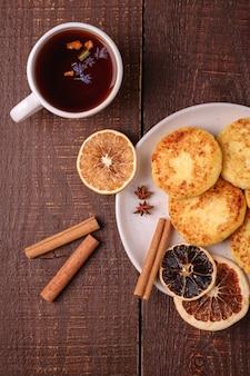 Beignets de fromage cottage avec thé aromatique noir chaud, ambiance de petit-déjeuner de noël avec anis, cannelle et agrumes séchés sur fond de bois, vue du dessus
