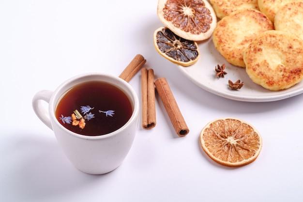 Beignets de fromage cottage avec thé aromatique noir chaud, ambiance de petit-déjeuner de noël avec de l'anis et de la cannelle sur fond blanc, vue d'angle