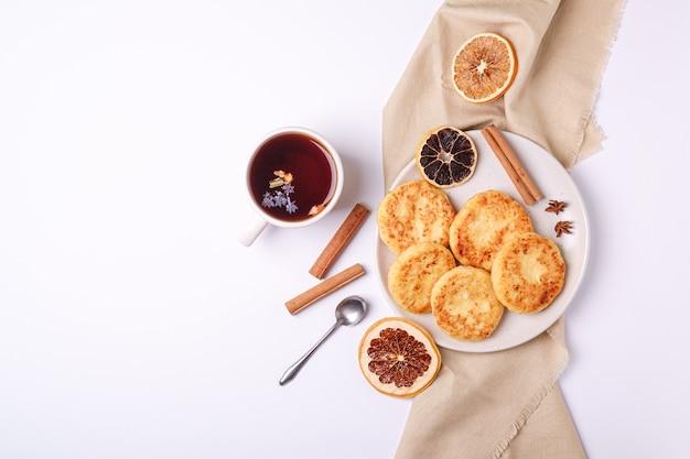 Beignets de fromage cottage avec thé aromatique noir chaud, ambiance de petit-déjeuner de noël avec de l'anis et de la cannelle sur une surface blanche, vue du dessus