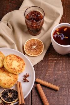 Beignets de fromage cottage avec thé aromatique noir chaud avec confiture de figues, humeur de petit-déjeuner de noël avec anis, cannelle et agrumes séchés sur fond de bois, vue d'angle