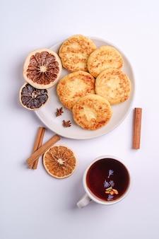 Beignets de fromage cottage avec thé aromatique noir chaud, petit-déjeuner de noël à l'anis et à la cannelle