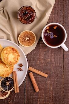 Beignets de fromage cottage avec thé noir aromatique chaud avec confiture de figues, humeur de petit-déjeuner d'hiver avec anis, cannelle et agrumes séchés