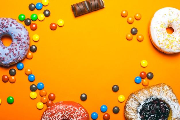Beignets avec glaçage coloré et cerises brioches avec du sucre en poudre. bonbons au chocolat de couleur sur un fond orange copie espace vue de dessus.