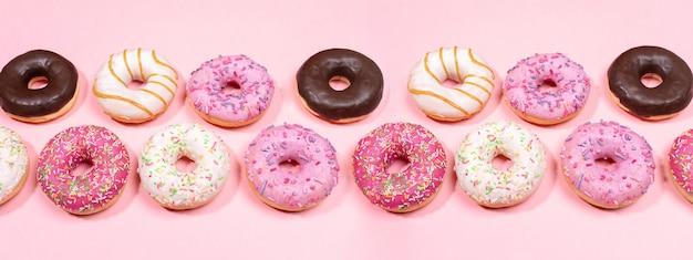 Beignets avec glaçure multicolore disposés en deux rangées sur fond rose tendance. bannière web créative.