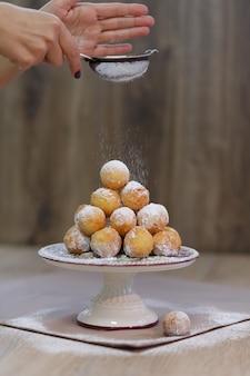 Beignets sur un plateau saupoudré de sucre en poudre