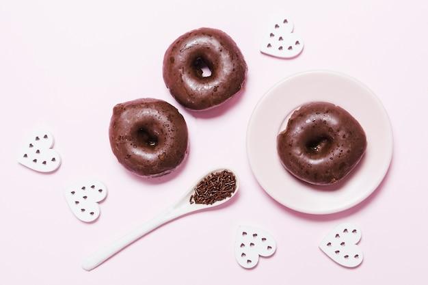 Beignets plats poser avec des coeurs de papier sur fond rose