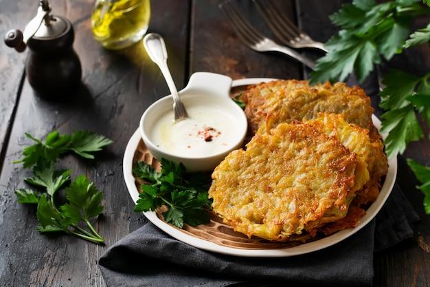 Beignets de pommes de terre draniki, crêpes de pommes de terre végétariennes, servies avec des herbes fraîches et sauce au yogourt à l'ail