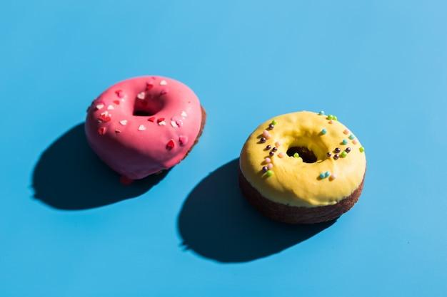 Beignets ronds colorés sur fond bleu clair. beignets sucrés. motif d'été à la mode d'été concept d'été minimal.
