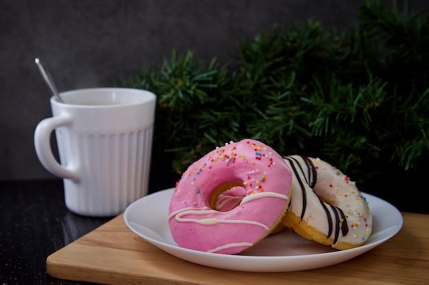 Beignets roses sur une assiette avec du café
