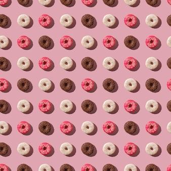 Beignets roses, vanille et chocolat avec des paillettes, modèle sans couture, dessert sucré glacé sur fond minimal rose, vue de dessus